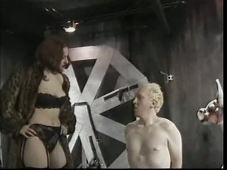 Redhead Dominatrix Teases with Pang