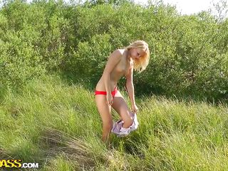a horny blonde beauty on a green field
