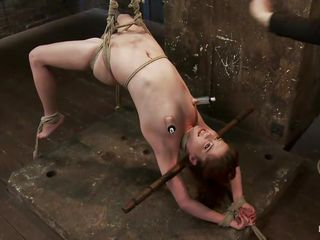 oiled chick hanging while receiving her punishment