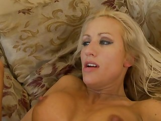 A blonde milf with implants gets fucked while she is on her back