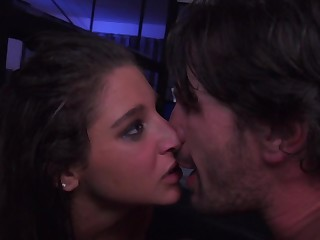 A brunette is kissed by her lover in a dark room in this scene
